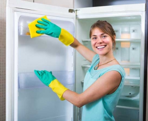 Smiling girl wiping fridge